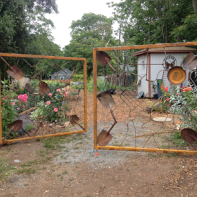 An artistic gate, slightly ajar, leading to the community garden.